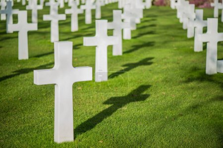 White crosses on graveyard with shadow