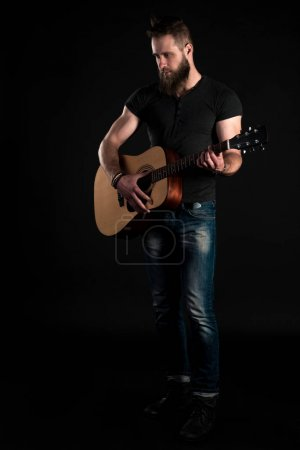 A charismatic and stylish man with a beard stands full-length and plays an acoustic guitar, on a black isolated background. Vertical frame