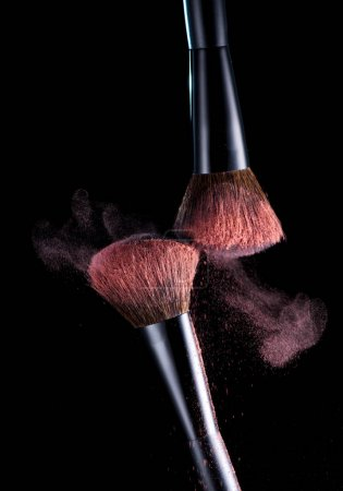 Makeup brushes with pink powder dust on a black background