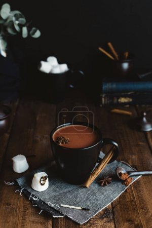 Mug of Hot Cocoa with Marshmallows and Cinnamon Sticks on Rustic Table