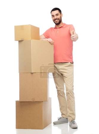 happy man with cardboard boxes showing thumbs up