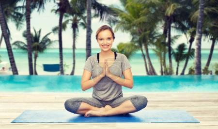 woman making yoga meditation in lotus pose on mat