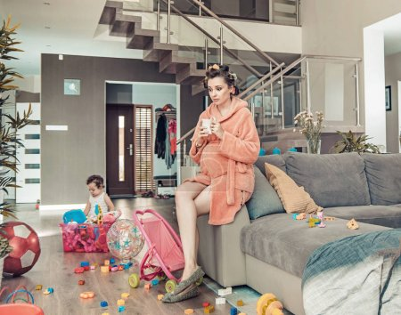 Photo for Young pregnant mother and her little daughter at home - Royalty Free Image