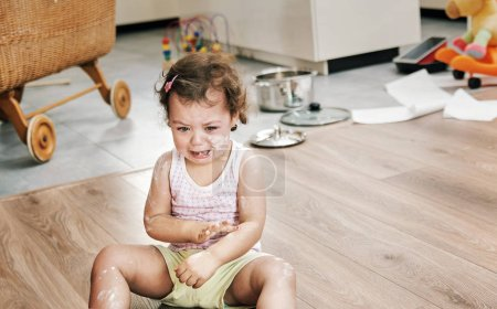 Photo for Naughty little girl sitting on the floor - Royalty Free Image
