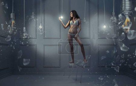 Photo pour Portrait d'art d'un sensuel brunettewoman tenant une ampoule électrique - image libre de droit