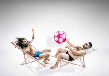 Photo pour Deux amis drôles, assis sur des chaises longues - image libre de droit