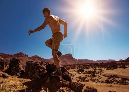Handsome, muscular man running on the desert