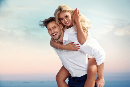 Handsome man carrying his girlfriend piggyback