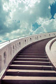 Stairs towards blue sky with clouds