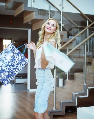 Blond pretty woman holding shopping bags