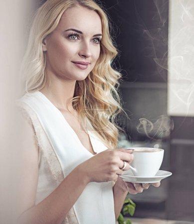 Porträt einer hübschen Blondine beim Kaffeetrinken