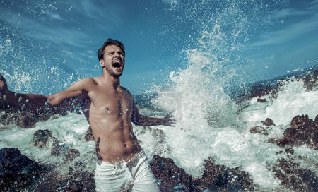 Portrait of a handsome man jumping into the sea water