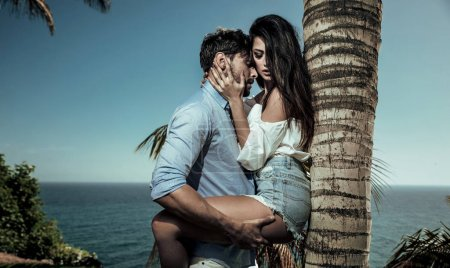 Photo for Portrait of two attractive lovers leaning on a palm tree - Royalty Free Image