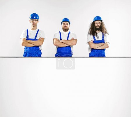 Photo for Three talented craftsmen with an empty, white board - Royalty Free Image