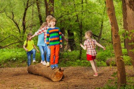 kids walking on log of tree