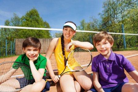 Tennis team sitting on clay court