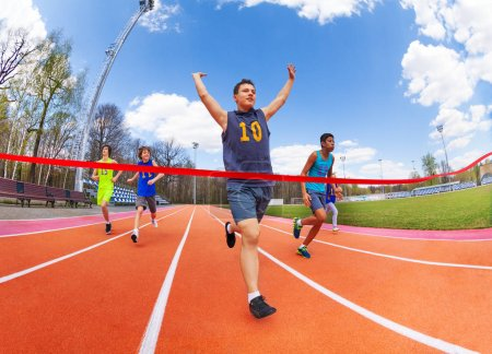 Photo for Portrait of teenage sprinter crossing finish line - Royalty Free Image