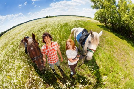 couple walking with purebred horses