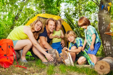 Young active family camping in forest