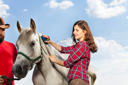 woman grooming her white horse
