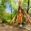 Cute girl in Indian costume standing at wigwam...