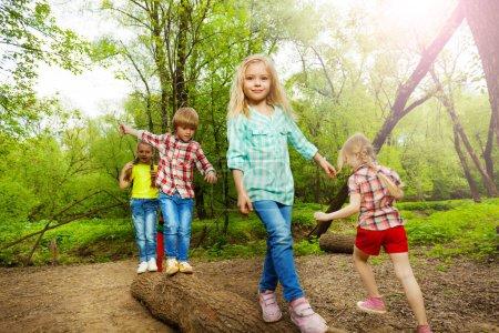 Happy kids walking on log