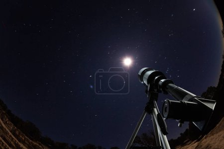 Telescope pointed to night sky and stars