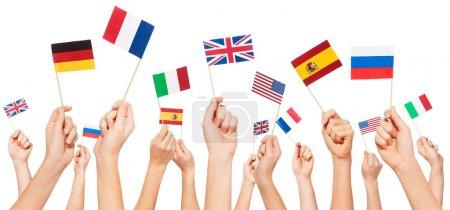 Photo pour Mains tenant des drapeaux en papier petit des Usa et les pays européens, isolés sur blanc - image libre de droit