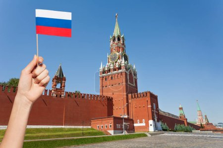 hand holding small Russian flag