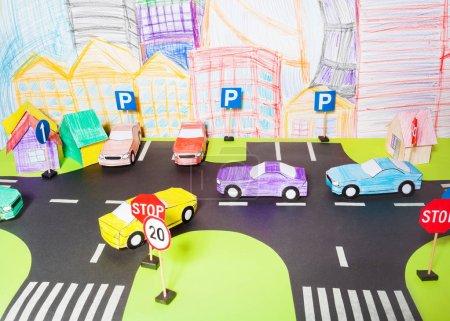 Photo pour Maquette de papier à la main circulation sur les routes avec des passages pour piétons, des panneaux, un parking et des voitures jouets en papier - image libre de droit