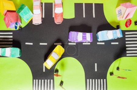 Photo pour Vue de dessus de la circulation de maquette de papier à la main sur les routes avec des passages pour piétons, des panneaux, un parking et des voitures jouets en papier - image libre de droit