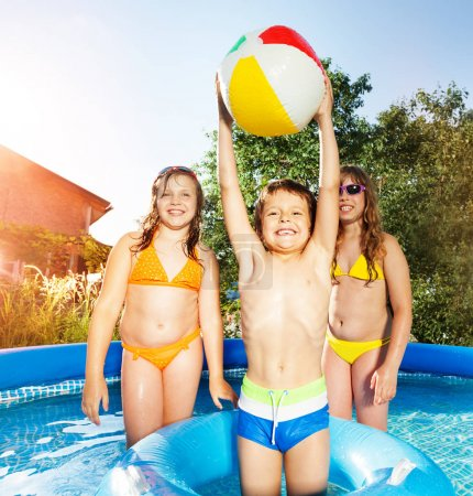 Happy kids playing in swimming pool