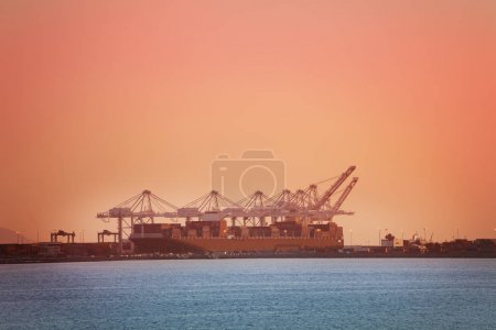 port with cranes at sunset