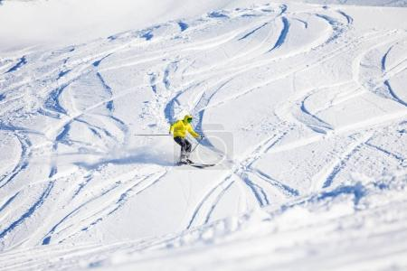 Sporty man skiing downhill