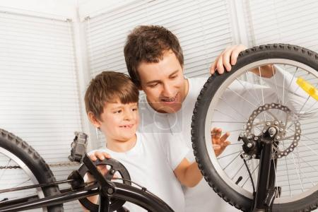 boy and father fixing bicycle
