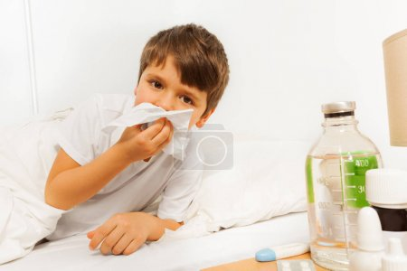 Sick boy blowing nose