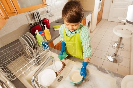 boy wash dishes with sponge
