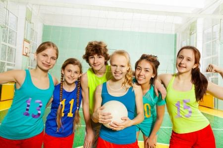 Photo for Close-up portrait of happy volleyball players holding ball, standing together in line in gymnasium - Royalty Free Image