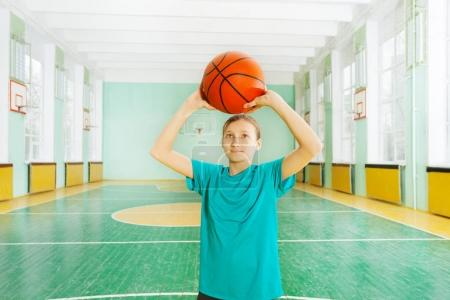 Photo for Portrait of happy girl standing with ball in sports hall - Royalty Free Image