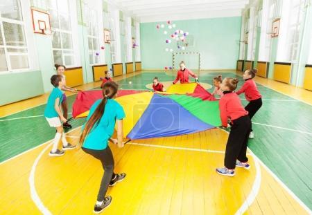 Photo pour Groupe de joyeux garçons et filles, jouer à des jeux de parachute en salle de sport - image libre de droit