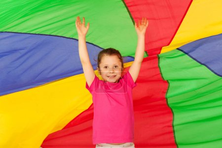 girl jumping under colored parachute