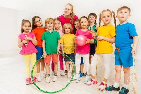 Photo pour Portrait de jeune femme sport enseignants et enfants heureux holding équipement de sport au gymnase - image libre de droit