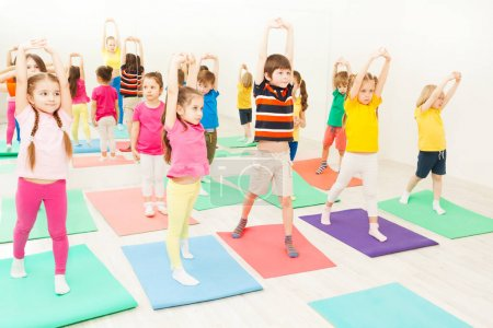 Photo for Portrait of happy kids practicing gymnastic exercises on mats at gym lesson - Royalty Free Image