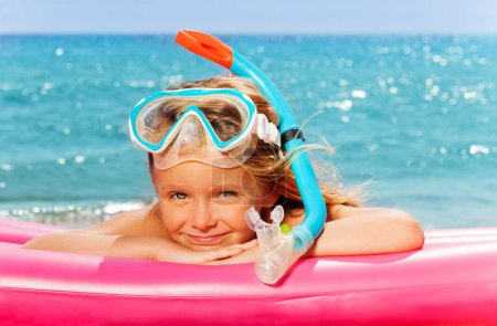 girl laying in snorkeling mask against sea