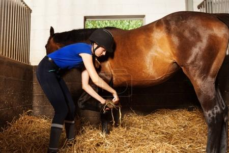 Horsewoman cleaning horses hoof at box stall