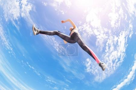 Low angle view of female athlete remaining stationary in air while jumping or running against cloudy sky