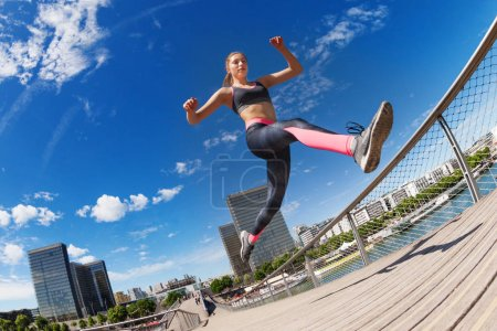 Female runner jumping while running against cityscape