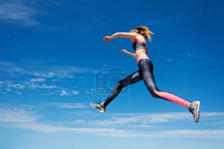 Low angle view of female athlete remaining stationary in air while jumping against blue sky