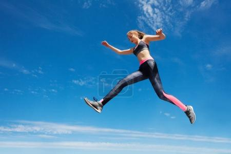 Low angle view sportswoman remaining stationary in air while jumping against blue sky