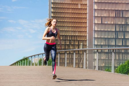 Sporty young woman running and sprinting outside at racetrack